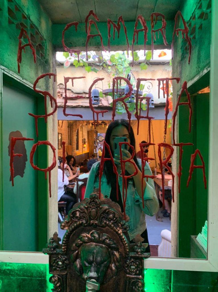 Espelho do lavabo da cafeteria Harry Potter em São Paulo, com a frase da abertura da câmara secreta