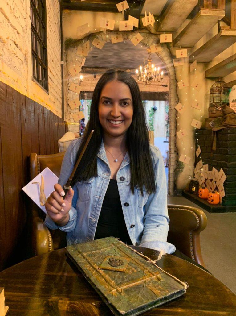 Mulher sentada na mesa e segurando uma varinha na cafeteria Harry Potter em São Paulo